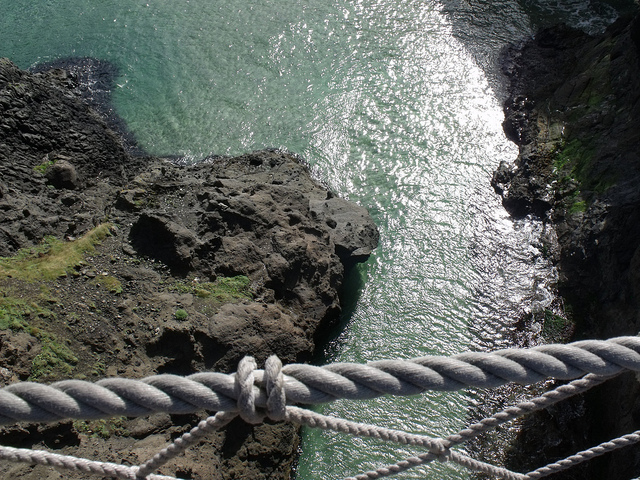looking into the ocean over the railing of a rope bridge