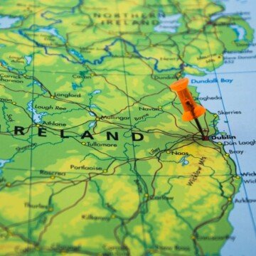 A green map drawing of Ireland with a paper pin marking the location of Dublin