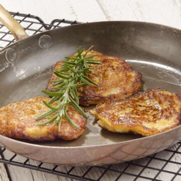 Three potato pancakes in a silver skillet with a thyme sprig