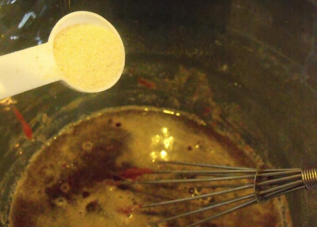 Onion powder in a teaspoon over a pot of gravy
