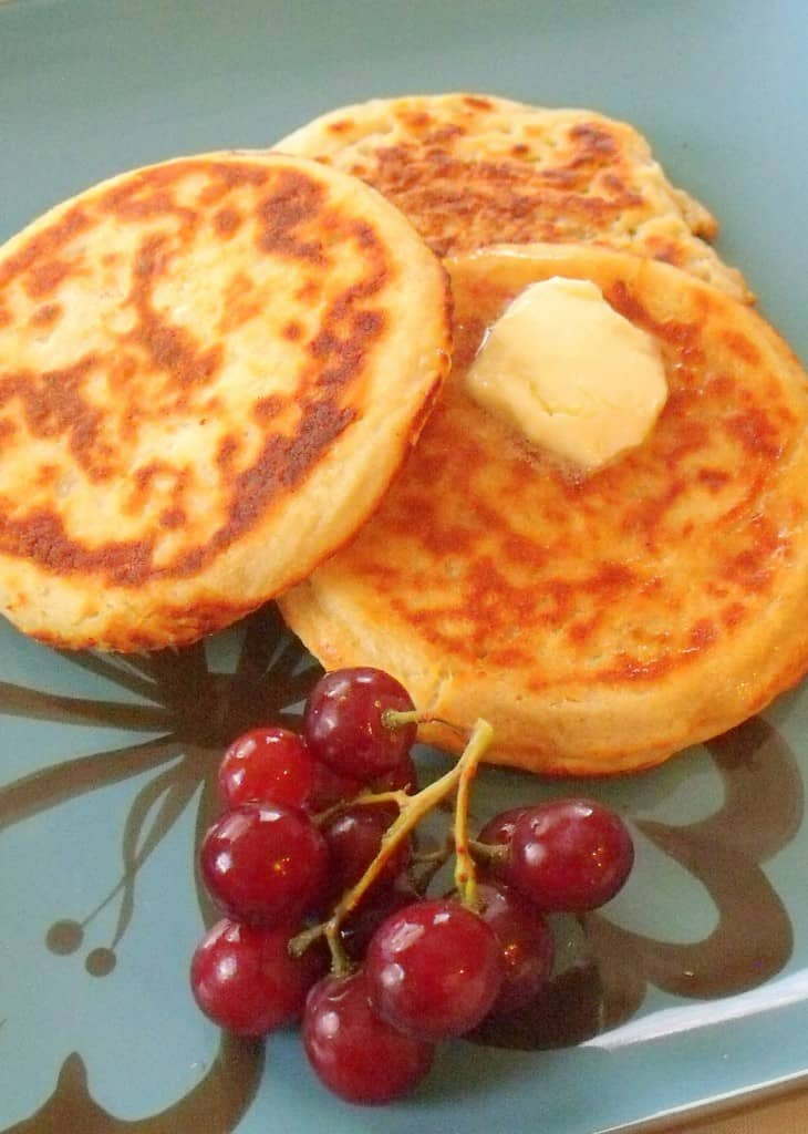 Three small boxty pancakes on a plate with grapes