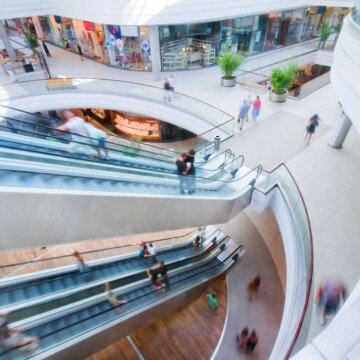 Looking down on two levels of escalators in a shopping mall