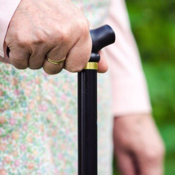 An hold woman holding the handle of a walking cane