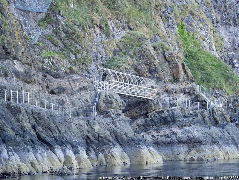 An iron bridge connects a railed walkway along cliffs