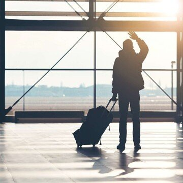 A silhouette of a man waving at the airport while holding a bag on wheels