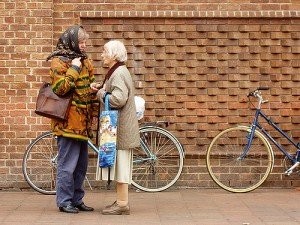 Two ladies chatting beside two bicycles leaning against a wall