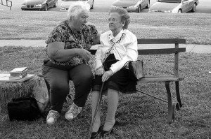 Two women sitting on a bench chatting