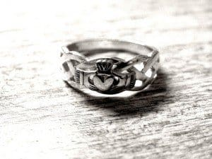 Claddagh ring in black and white on a wooden surface