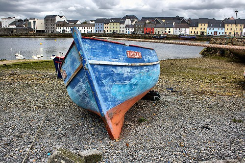 Blue boat on the shore near a pier and buildings