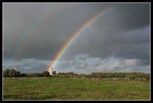 A rainbow's end landing on a round tower in Clarinbridge County Galway