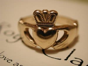 Gold Irish Claddagh ring with crown on a heart and held by two hands