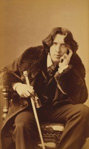 Photograph of Oscar Wilde wearing a fur collared coat and holding a cane