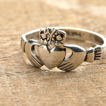A ring with two hands, a heart and a crown on a wooden surface