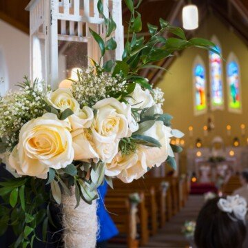 A bouquet of white roses in a vase inside a church