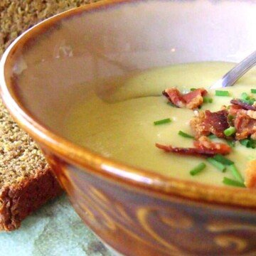 A brown bowl with potato and leek soup with a bacon and chive garnish