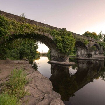 An arched stone bridge over a body of water