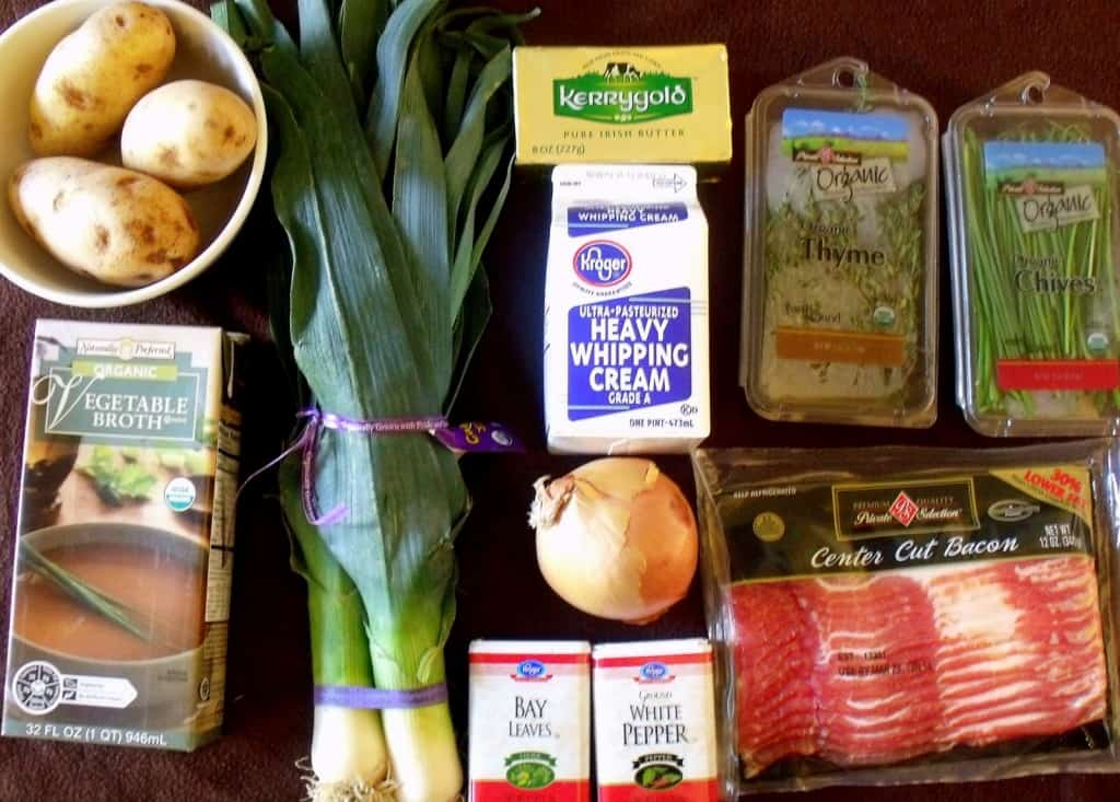 Ingredients for Irish potato and leek soup with potatoes, leeks, broth, herbs, onion, cream and butter.