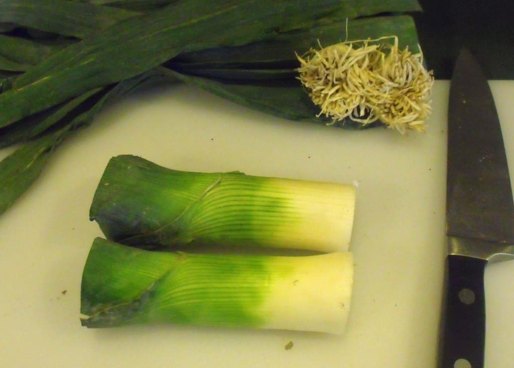 Two leeks with the upper leaves removed lying on a chopping board with a knife.