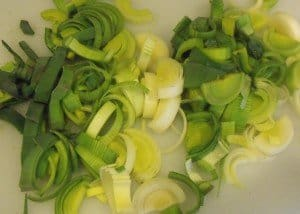 Sliced and chopped leeks on a white chopping board