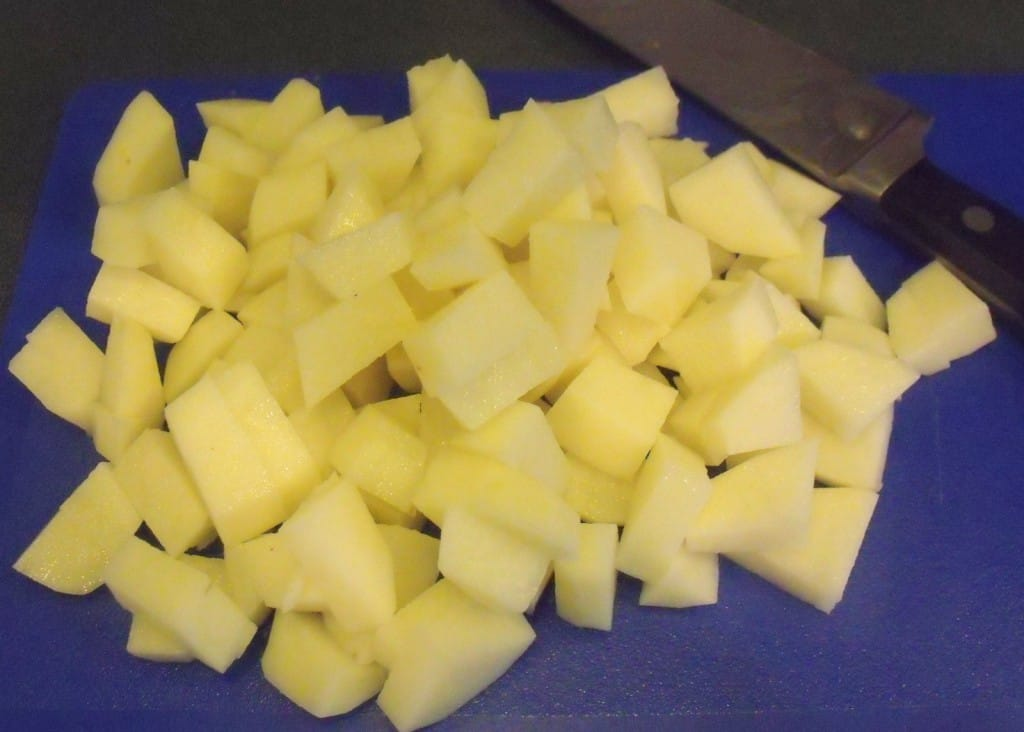 Chopped and diced potatoes on a blue chopping board beside a knife.