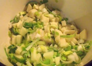 Chopped potatoes, leeks and onions sweating in the bottom of a large pot