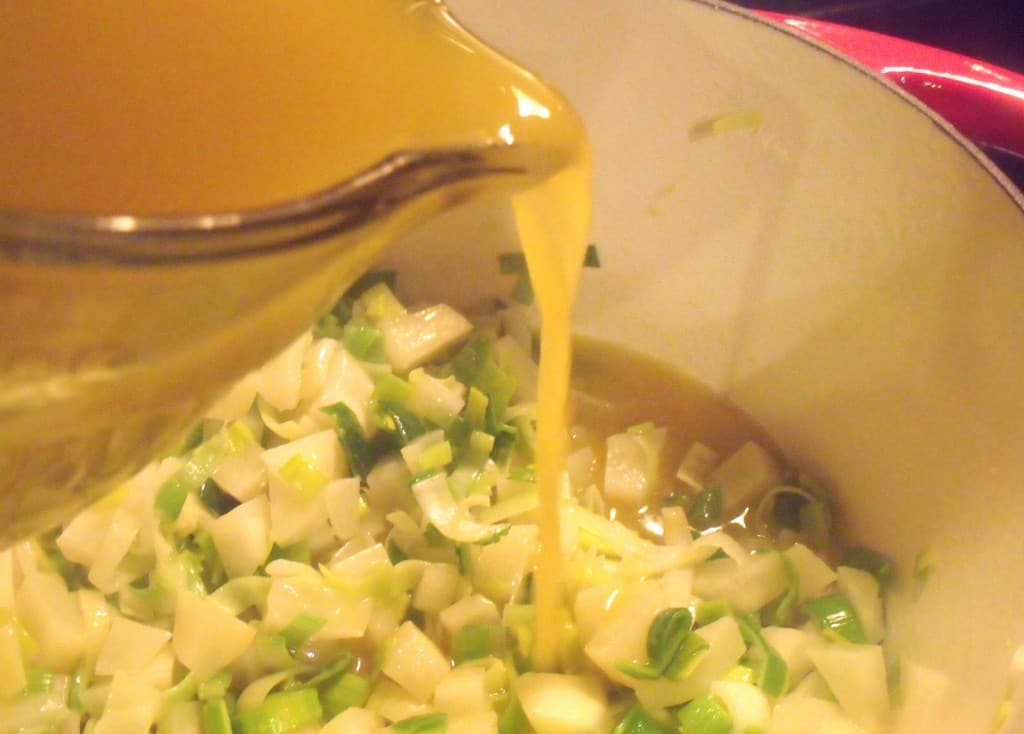Adding vegetable broth to potatoes, onions and leeks in a large soup pot.