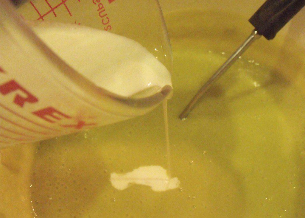 Adding heavy whipping cream to a pot of potato and leek soup.