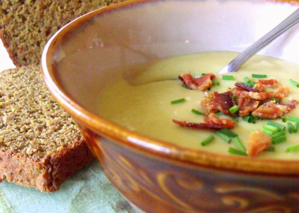 A brown rimmed bowl with a serving of potato and leek soup garnished with bacon bits and chives and served with sliced Irish brown bread.