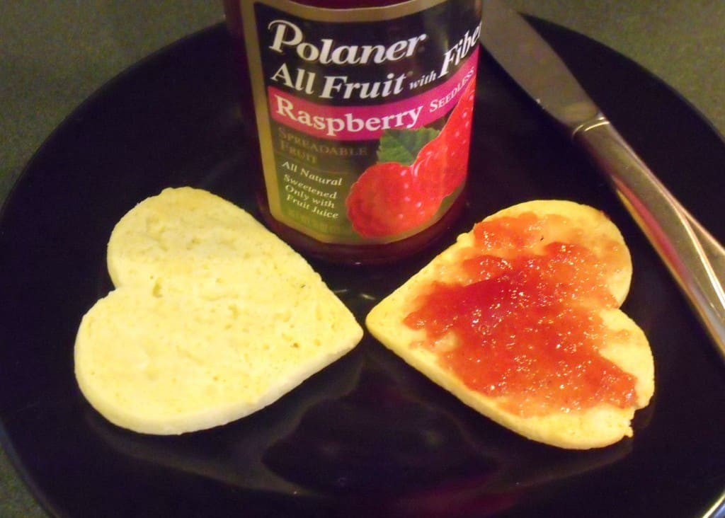 Two heart shaped cookies being spread with jam