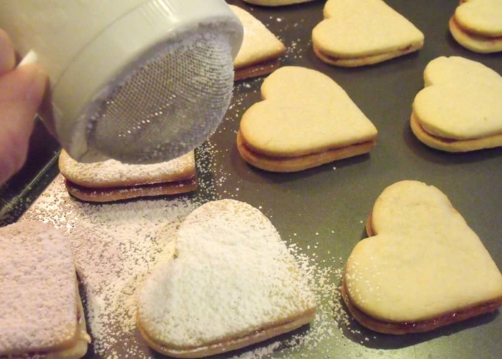 Heart shaped almond cookies with jam being dusted with sugar