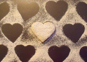 Marks on a board where sugar was dusted over heart shaped cookies