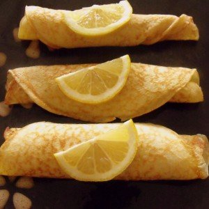 Three Irish pancakes on a plate with lemon slices for garnish