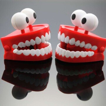 Red toy dentures with eyes facing each other on a reflective surface