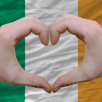 Two hands forming a heart over a green white and orange Irish flag