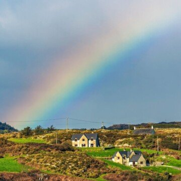 A rainbow arc over green and rocky fields and two homes
