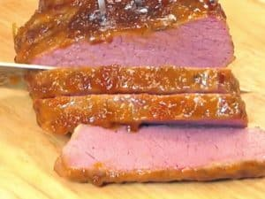 Cooked corned beef on a wooden chopping board being sliced with a knife
