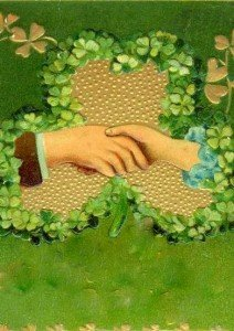 Man and woman shake hands over a golden shamrock