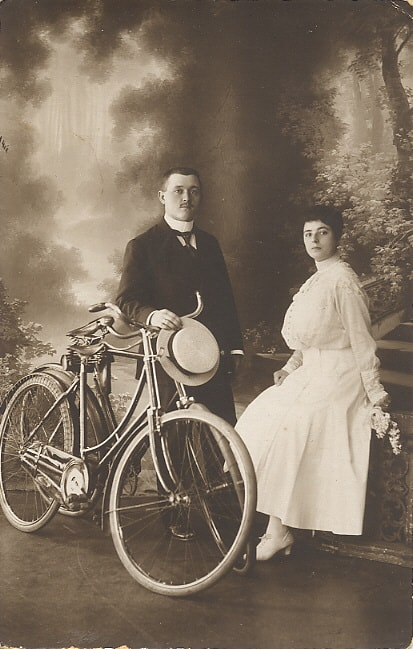 A vintage photo of a man and a woman standing next to a bicycle