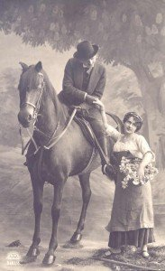 Black and white photo of a man on a horse holding a woman's hand