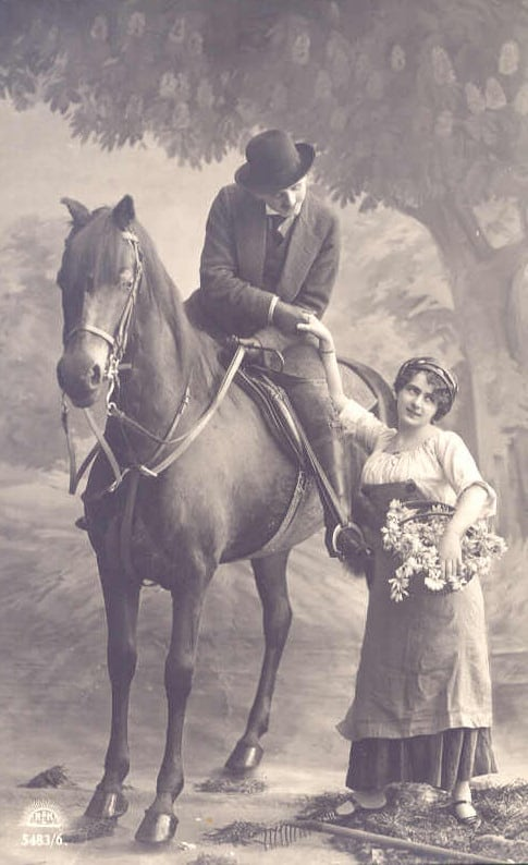 Black and white photo of a man on a horse holding a woman\'s hand