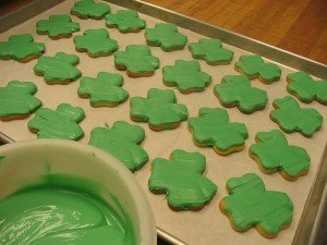 Shamrock cookies being covered in green icing