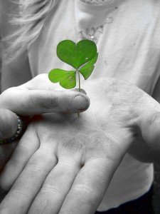 Holding a shamrock in the palm of a dirty hand