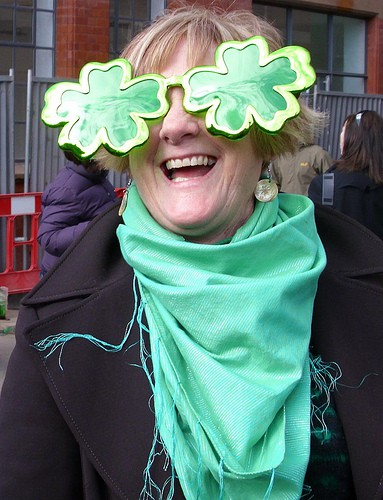 Woman in green scarf wearing oversized shamrock sun glasses