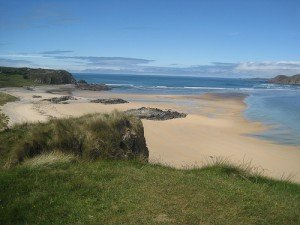 Sandy beach by sand dunes looking out across the Atlantic Ocean in Donegal Ireland