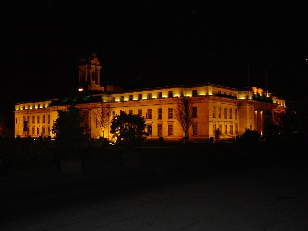 A large granite building lit up by orange lights in the dark of night