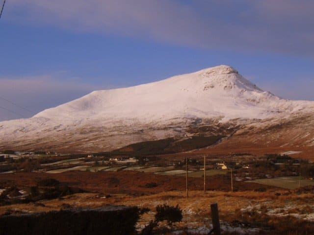 A flat topped mountain covered in snow