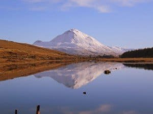A snowy mount Errigal reflecting in a mountain lake