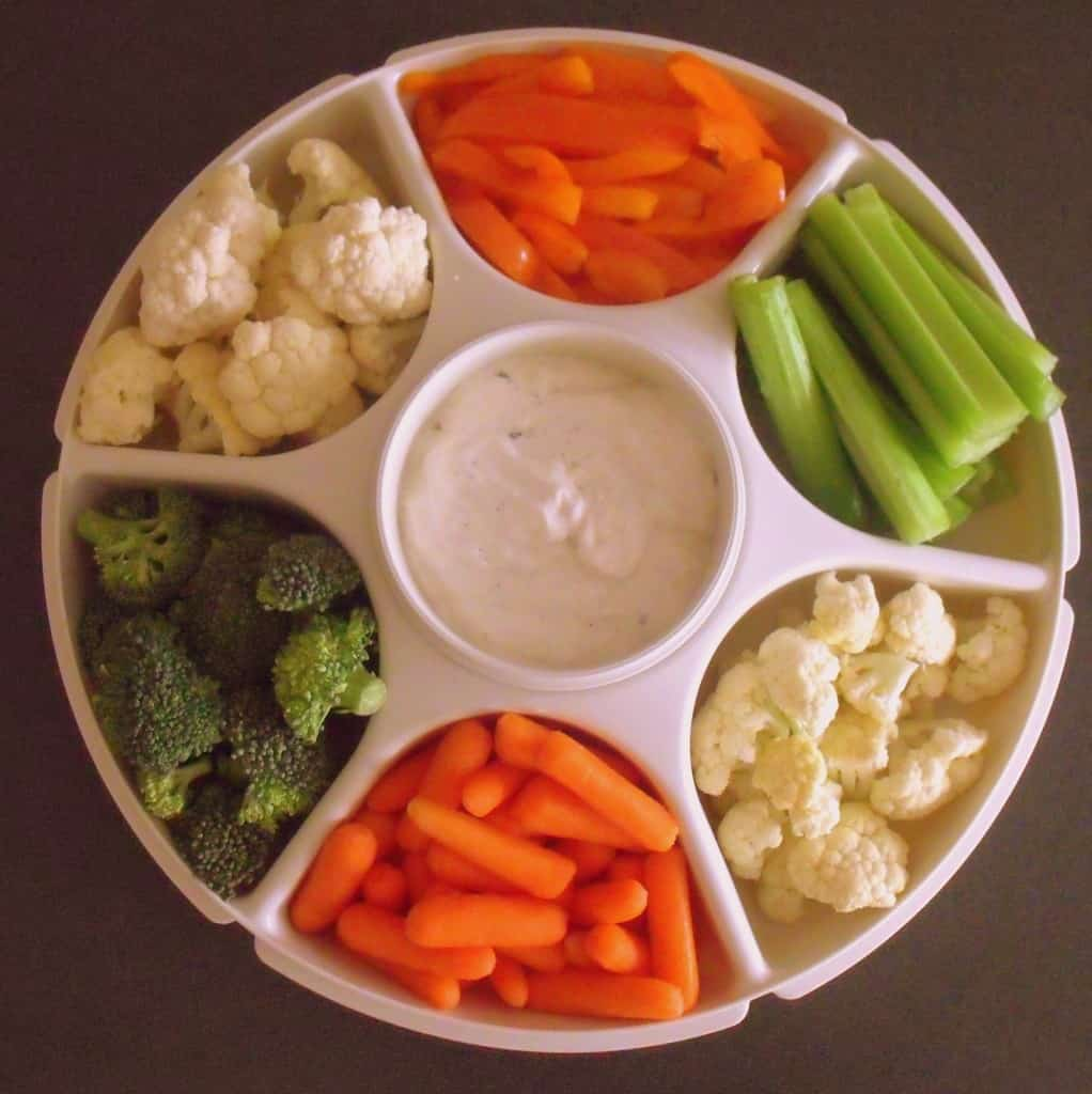 A circular separated veggie server with green, white and orange vegetables with ranch dip