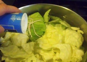 Adding salt to cabbage and water in a saucepan