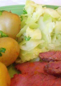 A serving of cabbage beside sliced corned beef and boiled potatoes